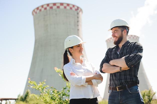 Due operai che indossano il casco protettivo lavorano alla centrale elettrica