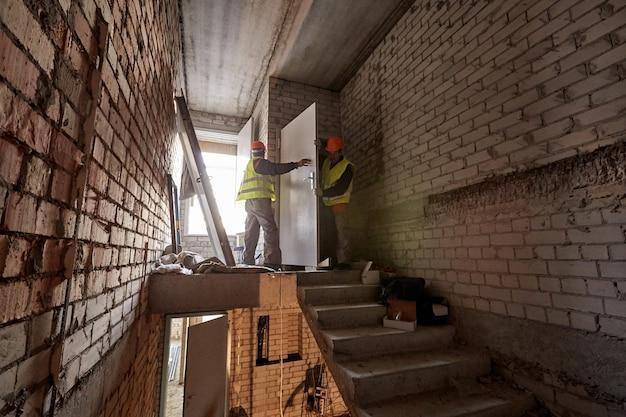 Due lavoratori in abiti da lavoro e elmetti stanno installando una porta in una tromba delle scale incompiuta di un grattacielo in costruzione Foto Premium