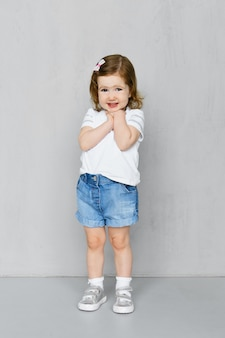 Ragazza di due anni in pantaloncini di jeans e t-short in posa in studio