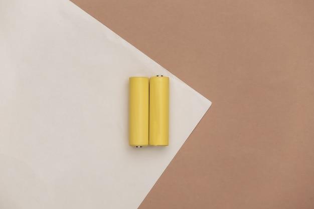 Due batterie aa gialle su sfondo beige marrone. vista dall'alto