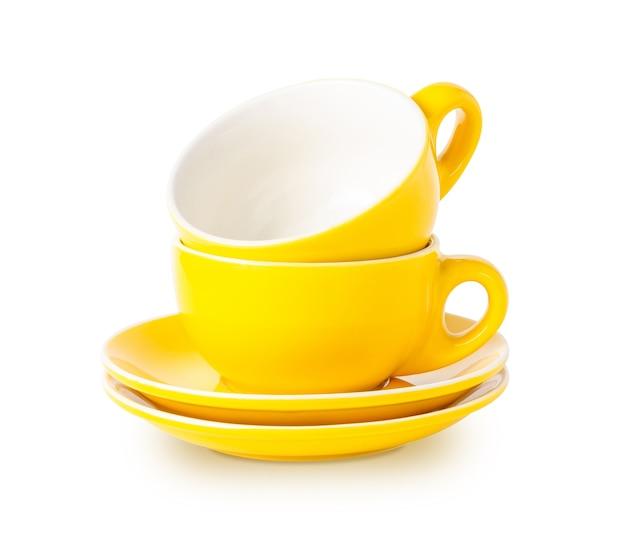 Due tazze gialle su piattini in una pila isolata su sfondo bianco