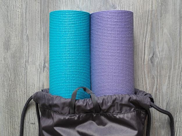 Due stuoie di yoga in una borsa grigia. tappetini per pilates o fitness in palestra