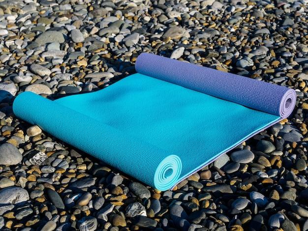 Due stuoie di yoga sul primo piano dei ciottoli di mare