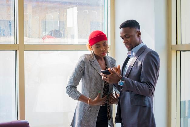 Due giovani soci in affari africani che discutono di ciò che hanno visto sul loro cellulare.