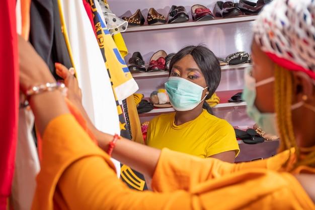 Due giovani donne africane che acquistano vestiti in un negozio locale