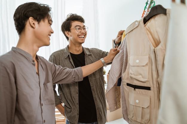 Due giovani imprenditori asiatici in chat sul loro prodotto di abbigliamento