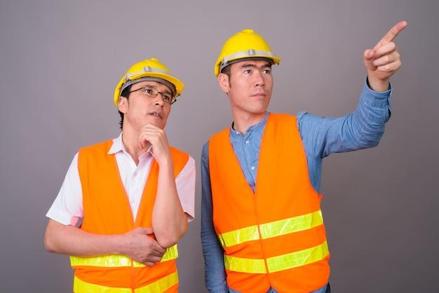 Operaio edile di due giovani uomini asiatici insieme contro il muro grigio