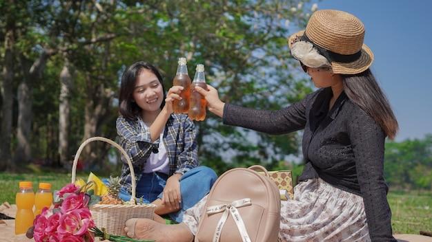 Due giovani donne asiatiche esultano bevendo mentre sono in vacanza in riva al lago
