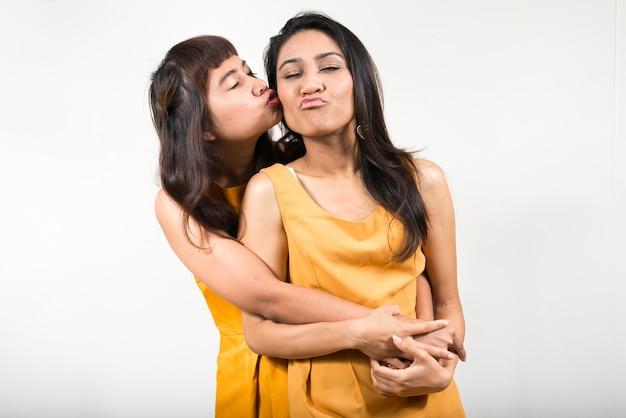 Due giovani donne asiatiche insieme contro uno spazio bianco