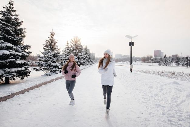 Due giovani ragazze atletiche che corrono nel parco in una soleggiata giornata invernale. uno stile di vita sano.