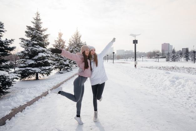 Due giovani ragazze atletiche che camminano e praticano sport in una soleggiata giornata invernale. uno stile di vita sano.