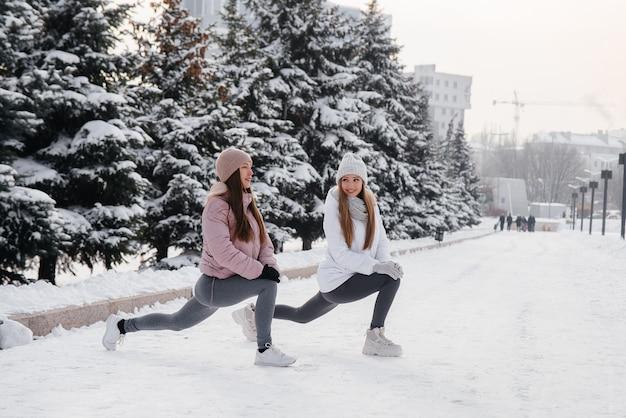 Due giovani ragazze atletiche fanno un riscaldamento prima di correre in una soleggiata giornata invernale. uno stile di vita sano.