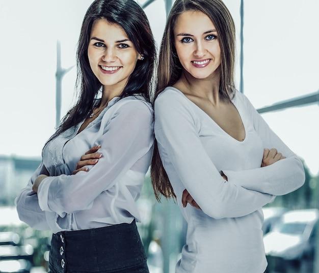 Due giovani, attraenti donne d'affari di successo in piedi braccia cr