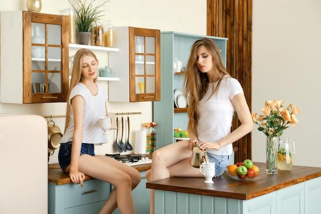 Due giovani donne attraenti che bevono caffè e parlano in cucina