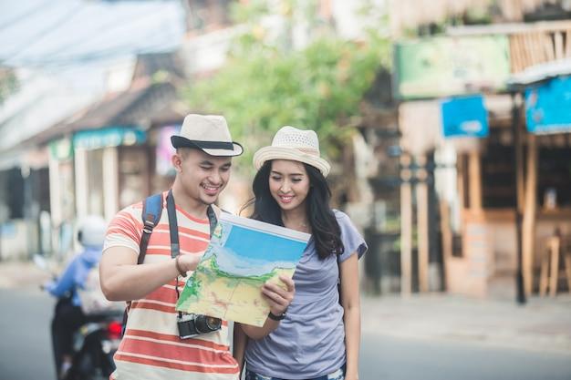 Due giovani viaggiatori con zaino e sacco a pelo che cercano direzione sulla mappa di posizione mentre