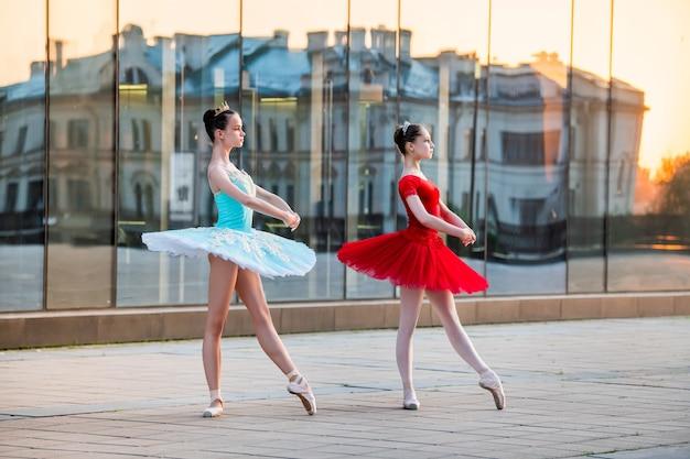 Due giovani ballerine in un tutù rosso e blu brillante stanno ballando sullo sfondo del riflesso del tramonto della città