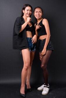 Due giovani belle donne transgender asiatiche insieme contro il muro nero