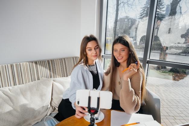 Due giovani belle ragazze sono sedute in un bar, registrano video blog e comunicano sui social network.