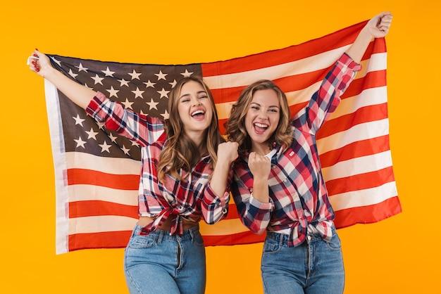 Due giovani belle ragazze che indossano camicie a quadri sorridenti e bandiera americana insieme isolate