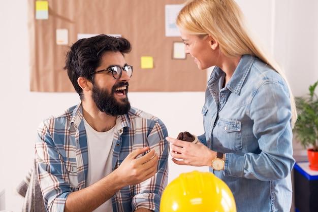 Due giovani ingegneri felici belli in ufficio che tengono un muffin in una pausa ridendo e chiacchierando.