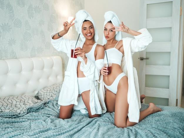 Due giovani belle donne sorridenti in accappatoi bianchi e asciugamani sulla testa