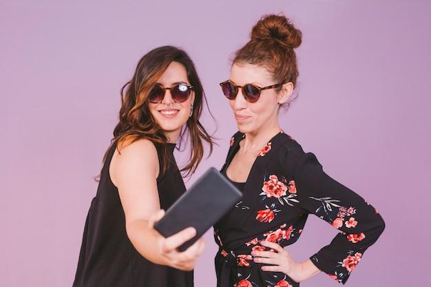 Due giovani belle donne divertendosi prendendo un selfie con il telefono cellulare. al chiuso. sfondo viola. abbigliamento casual. divertimento, felicità e stile di vita. occhiali da sole moderni