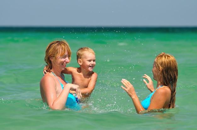 Due giovani donne bionde e piccolo ragazzo in piedi e godendo di essere in acqua in una limpida giornata di sole estivo. felicità, vacanze e concetto di libertà
