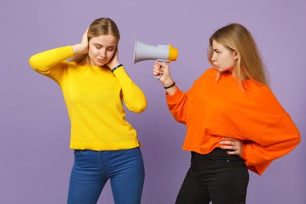 Due giovani sorelle gemelle bionde in abiti colorati che coprono le orecchie con le mani, urlano sul megafono isolato sulla parete blu viola pastello. concetto di stile di vita familiare di persone. . Foto Premium