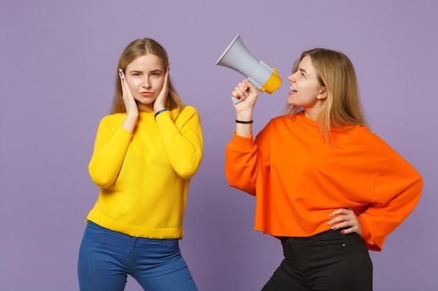 Due giovani sorelle gemelle bionde in abiti colorati che coprono le orecchie con le mani, urlano sul megafono isolato sulla parete blu viola pastello. concetto di stile di vita familiare di persone. .