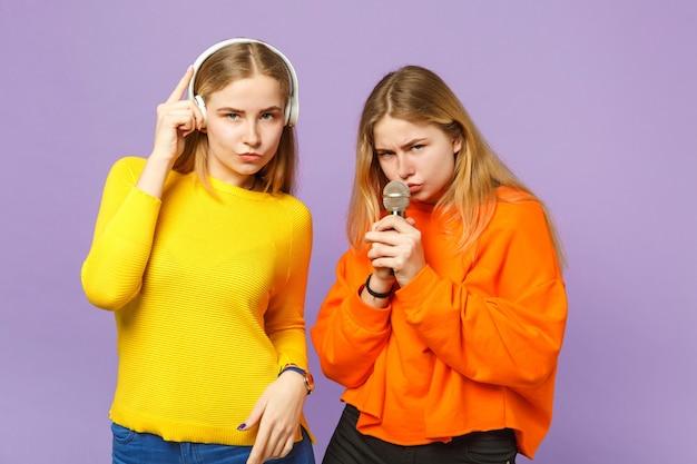 Due giovani sorelle gemelle bionde in abiti colorati ascoltano musica con le cuffie, cantano una canzone nel microfono isolato sulla parete blu viola. concetto di stile di vita familiare di persone.