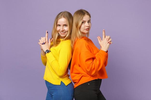 Due giovani sorelle gemelle bionde in abiti colorati in piedi schiena contro schiena, tenendo le dita come una pistola isolata sulla parete blu viola pastello. concetto di stile di vita familiare di persone.