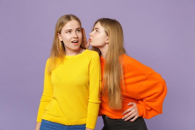 Due giovani sorelle gemelle bionde in abiti colorati che sussurrano pettegolezzi e raccontano il segreto con il gesto della mano isolato sulla parete blu viola. concetto di stile di vita familiare di persone.