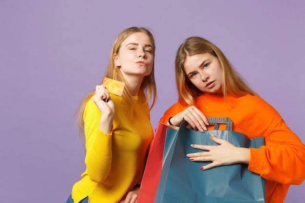 Due giovani sorelle gemelle bionde in abiti vivaci in possesso di carta di credito, borsa pacchetto con acquisti dopo lo shopping isolato su parete blu viola. concetto di famiglia di persone.
