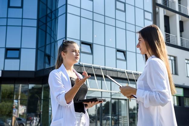 Due giovani donne d'affari che negoziano vicino al centro affari business