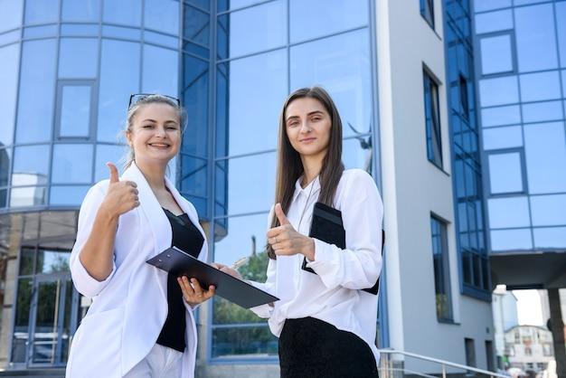 Due giovani donne d'affari in posa fuori dall'edificio degli uffici