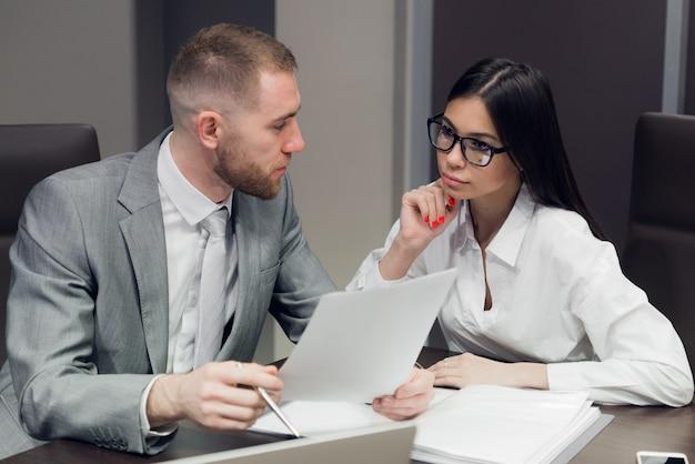Due giovani uomini d'affari che discutono di lavoro durante una presentazione aziendale in sala conferenze