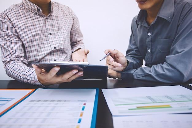 Due giovane uomo d'affari che esamina il documento di dati alla riunione per discutere della situazione sul mercato