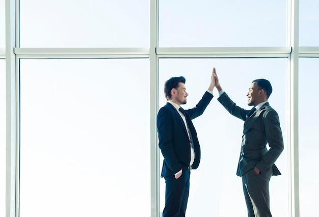 Due giovani uomini d'affari si stringono la mano.