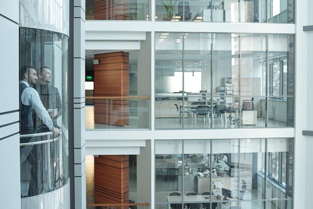 Due giovani imprenditori si muovono in ascensore all'interno di un grande business center contemporaneo composto da più piani