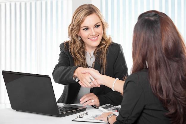 Due giovani imprenditrice stringendo la mano, isolato
