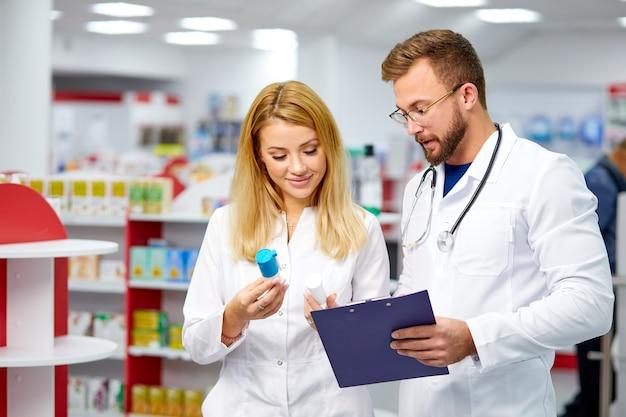 Due giovani colleghi caucasici in farmacisti bianchi dell'abito medico che soddisfano una prescrizione