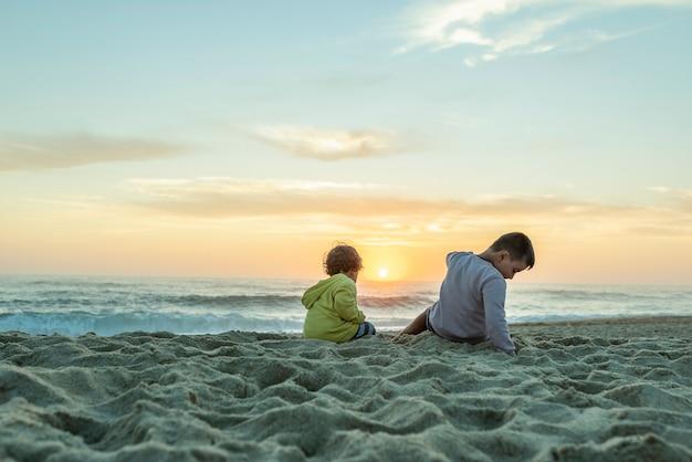 Due giovani ragazzi caucasici al tramonto sulla spiaggia settentrionale in portogallo che puntano al sole al tramonto.