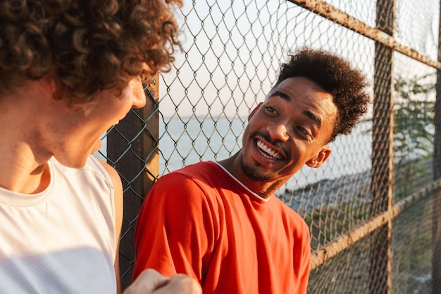 Due giovani giocatori di pallacanestro multietnici allegri degli uomini