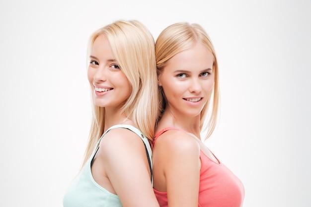 Due giovani donne allegre vestite di magliette. isolato sopra il muro bianco