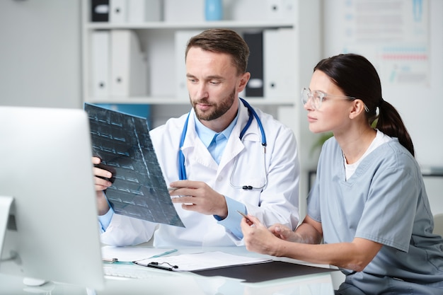 Due giovani medici in uniforme seduti alla scrivania davanti al monitor del computer, discutono della radiografia del paziente e si consultano in studio medico