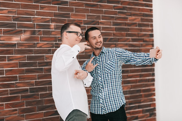 Due giovani colleghi di lavoro che prendono selfie in piedi in ufficio .persone e tecnologia
