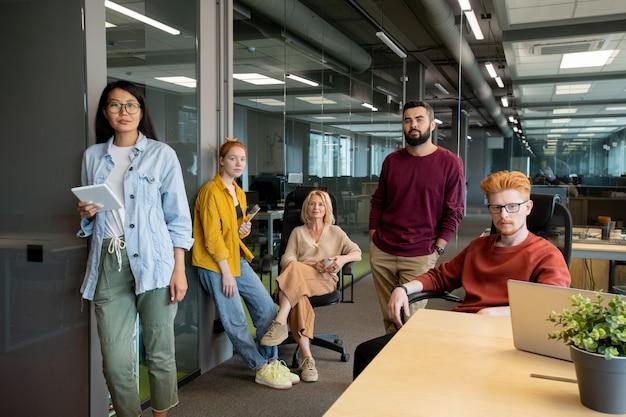 Due giovani uomini d'affari fiduciosi e tre donne d'affari interculturali in abbigliamento casual ti guardano mentre lavori in un grande ufficio moderno