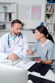 Due giovani medici fiduciosi in uniforme seduti alla scrivania davanti al monitor del computer, discutendo di documenti medici e consulenze