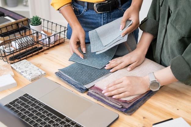 Due giovani designer creativi contemporanei di interni che scelgono campioni di tessuto per mobili per appartamento moderno o casa davanti al laptop