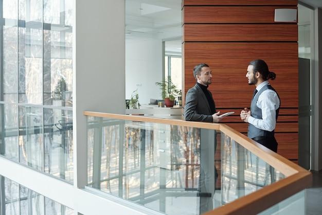 Due giovani uomini d'affari eleganti contemporanei che discutono i termini del nuovo affare alla riunione all'interno del grande centro di affari
